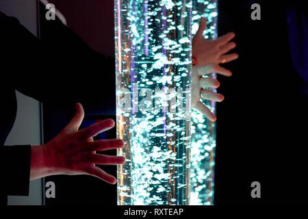 Therapie sensorische Stimulierung multi sensorische Zimmer, Frau Interaktion mit farbigen Lichtern bubble Röhrenlampe während der Therapie healthcare Seniorenheim sessi - Stockfoto
