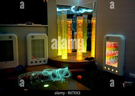 Therapie sensorische Stimulierung multi sensorische Zimmer mit bunten Lichtern bubble Röhrenlampe während der Therapie healthcare Seniorenheim Sitzung - Stockfoto