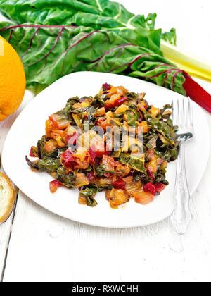 Warme Mangold Salat mit Orangen und Zwiebel in eine Platte, Brot, Gabel auf einem Holzbrett Hintergrund - Stockfoto