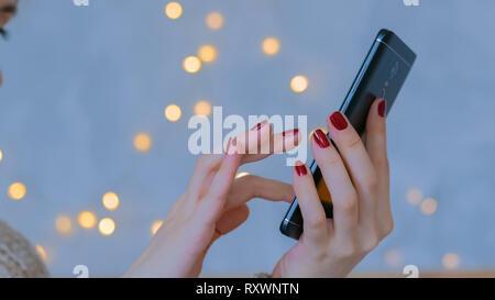 Frau mit vertikalen BlackBerry-Smartphone zu Hause - Stockfoto