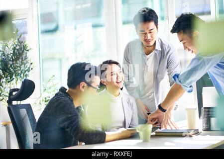 Gruppe von vier glücklichen jungen asiatischen Führungskräfte gemeinsam Treffen im Büro diskutieren im Büro. - Stockfoto