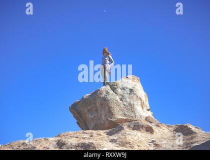 Eine junge Frau auf einem Boulder liegt direkt unterhalb des Tages Mond ausgerichtet. - Stockfoto
