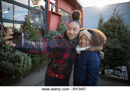 Schwestern mit Kamera Handy unter selfie am Weihnachtsbaum Markt - Stockfoto