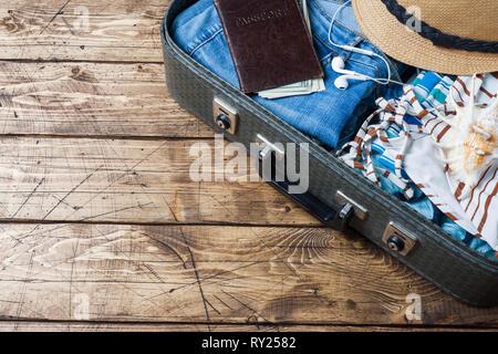 Reisevorbereitungen Konzept mit Koffer, Kleidung und Zubehör an einem alten Holztisch. Ansicht von oben Kopieren, - Stockfoto