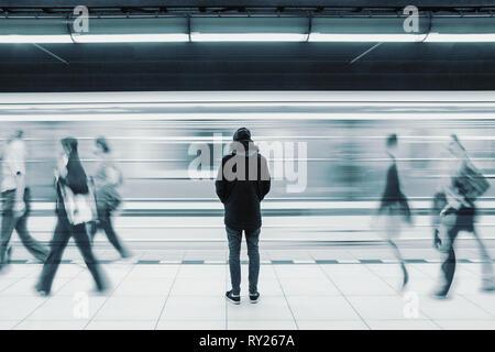 Lange Belichtung Bild mit einsamen Jungen Mann erschossen, von hinten an der U-Bahn station mit verschwommenen fahrenden Zug und nur wenige Leute im Hintergrund - Stockfoto