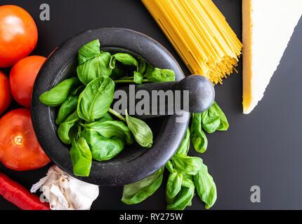 Vorbereitung italienische Pasta mit frischem Basilikum in Mörtel, Tomaten, Knoblauch, Pfeffer und Parmesan auf dunklen Küche Zähler