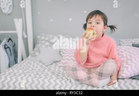 Kleines Mädchen isst einen Apfel - Stockfoto