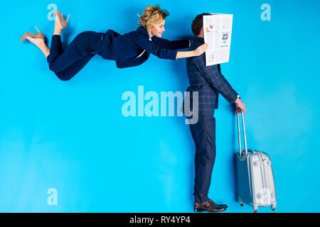 Frau posiert hinter Mann mit Koffer und halten die Zeitung in der Nähe von seinem Gesicht auf blauem Hintergrund - Stockfoto