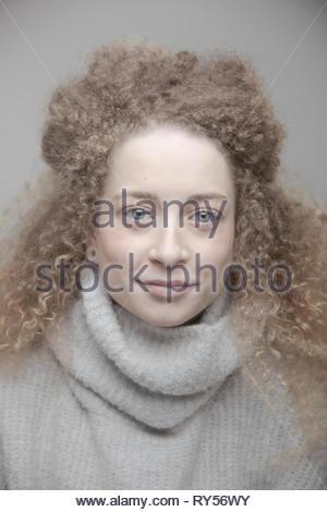Portrait zuversichtlich, schöne junge Frau mit langen, lockigen blonden Haar - Stockfoto
