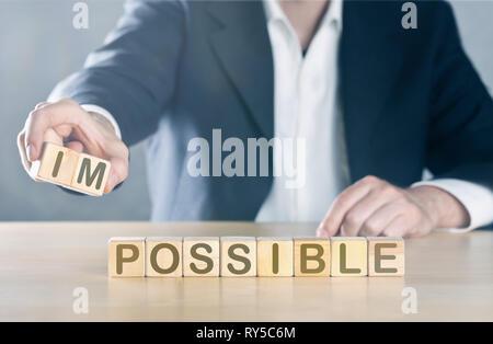 Business Mann legt in ersten zwei Buchstaben aus dem Wort nicht möglich, sodass es möglich wird; Management oder Lösungsfindung Konzept, blau getönt mit lig - Stockfoto
