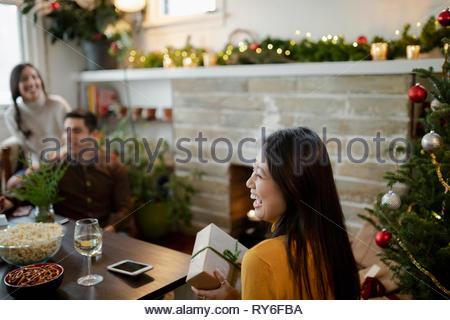 Glückliche junge Frau Eröffnung Weihnachten Geschenke mit Freunden im Wohnzimmer - Stockfoto