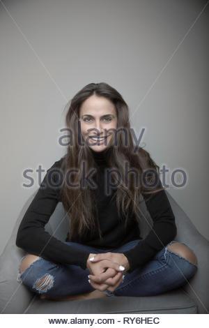 Portrait zuversichtlich glückliche junge brünette Frau in zerrissenen Jeans und Pullover - Stockfoto