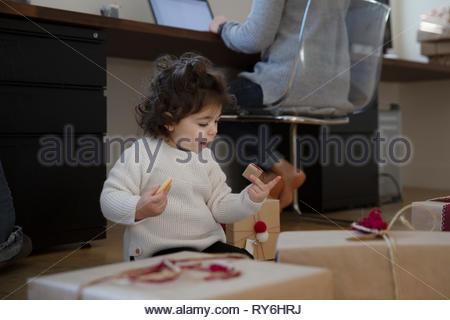 Latina toddler girl Cookies essen Neben Weihnachten Geschenke auf dem Boden - Stockfoto
