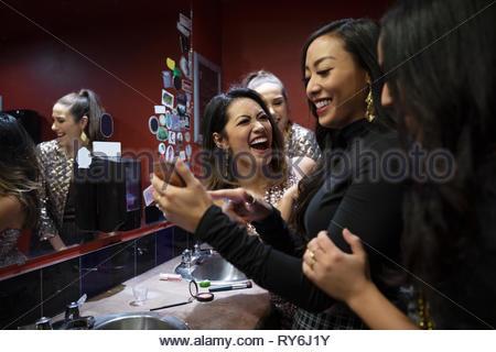 Lachende Frauen Freunde mittels Smart Phone in Nachtclub Badezimmer - Stockfoto