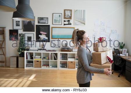 Junge Frau, die Weihnachtsgeschenke im Studio - Stockfoto