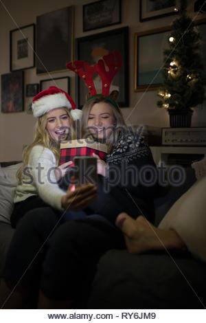Festliche junge Frauen Freunde Weihnachten zu feiern, wobei selfie mit Kamera Handy - Stockfoto