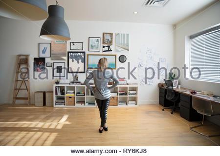 Junge Frau am Rahmen an der Wand, im Studio - Stockfoto