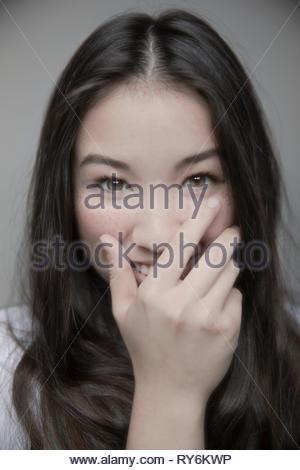 Portrait schöne Brünette junges Mädchen mit braunen Augen lachend mit der Hand über den Mund - Stockfoto