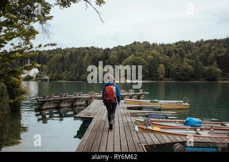 Volle Länge Rückansicht der weiblichen Backpacker zu Fuß auf hölzernen Pier über den See im Wald - Stockfoto
