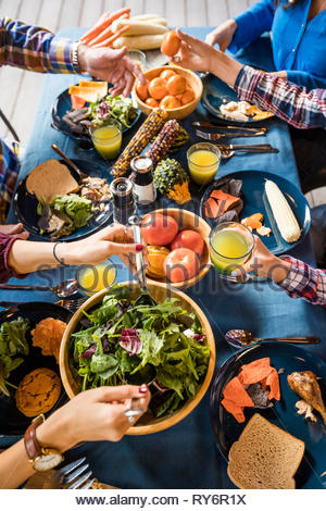 7/8 Händen der Familie Mittagessen auf dem Tisch im Hof - Stockfoto