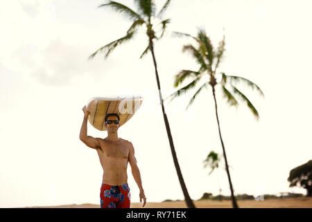 Mitte der erwachsene Mann mit einem Surfbrett auf seinem Kopf. - Stockfoto