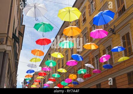 Bunte schwebende Schirme zwischen Gebäuden, Genua, Ligurien, Italien - Stockfoto