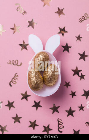 Gold Glitzer Eier in einem weißen Osterhase ei Form mit Ohren - Stockfoto