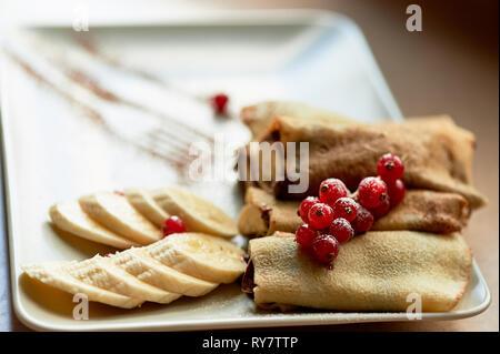 Dessert - heißen Pfannkuchen mit Nutella und Banane. Mit korinthen eingerichtet. süße Nachspeise. - Stockfoto