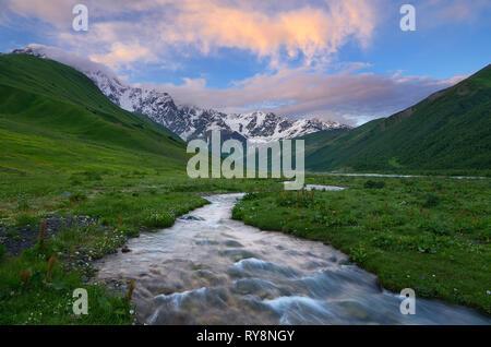 Fluss in den Bergen. Sonnenuntergang mit schönen Wolken. Sommer Landschaft. Main kaukasischen Ridge. Zemo Swanetien, Georgien - Stockfoto