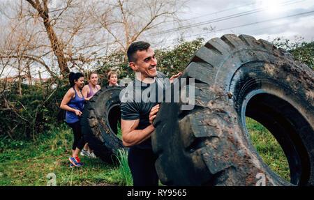 Teilnehmer in einen Hindernisparcours drehenden Rad