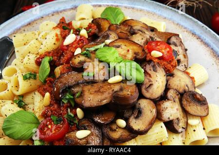 Penne Pasta Rigatoni in Tomatensauce mit Pilzen, Tomaten mit Petersilie und Basilikum eingerichtet - Stockfoto