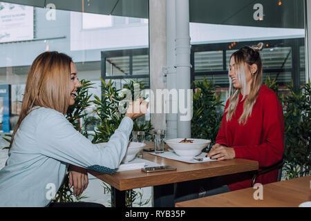 Weibliche Freunde gemeinsamen Mittagessen in das moderne Interieur des Restaurants. - Stockfoto