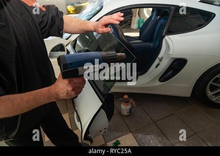 Der Assistent für die Installation von zusätzlicher Ausrüstung Stöcke eine Tönung Film auf der Vorderseite Glas des Auto- und trocknen Sie das Glas mit einem industrietrockner an der - Stockfoto