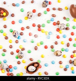 Kreative, oben flach Urlaub Zusammensetzung Ostern Wachtel, Schokolade, Eier, bunte Bonbons auf weißem Holz- Background Copy space Vorlage Ostern da - Stockfoto