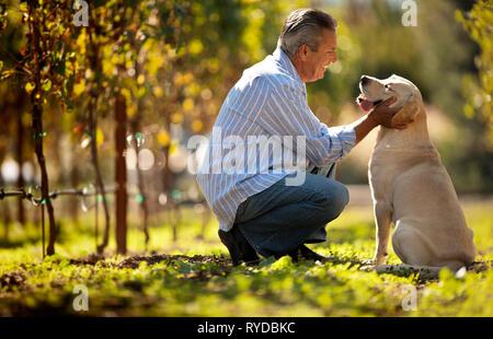 Reifer Mann zusammengekauert Neben seinem Hund im Weinberg. - Stockfoto