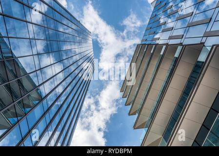 Wolken im blauen Himmel im Windows der Wolkenkratzer von unten reflektiert, ein horizontales Bild einer urbanen Landschaft