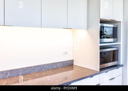 Moderne weiße minimalistische Küche verfügt über Schränke mit Granit Arbeitsplatte und Mikrowelle Toaster mit leeren Platz im Büro oder Zuhause. - Stockfoto