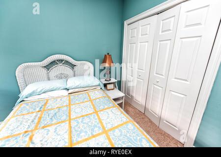 Saubere Bettwäsche mit Kopfteil Nachttisch und Lampe mit Vintage Strand Thema dekorative Blau Grün kissen im Schlafzimmer in der Inszenierung Modell Home Haus - Stockfoto
