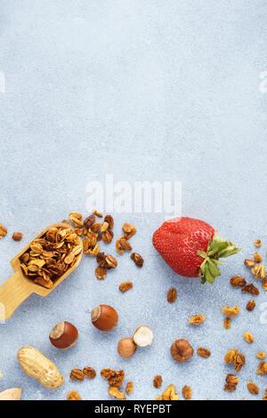 Müsli, Erdbeeren und Zutaten - Hafer, verschiedene Nüsse und Honig. Gesundes Frühstück Hintergrund mit kopieren. - Stockfoto