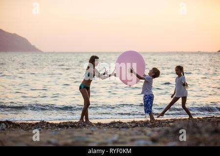Drei Kinder beim Spielen mit riesigen rosa Ballons am Strand bei Sonnenuntergang - Stockfoto