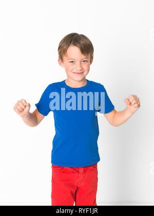 Sechs Jahre alten Jungen in roten Hosen und blaue T-Shirt ist vor weißem Hintergrund posiert - Stockfoto