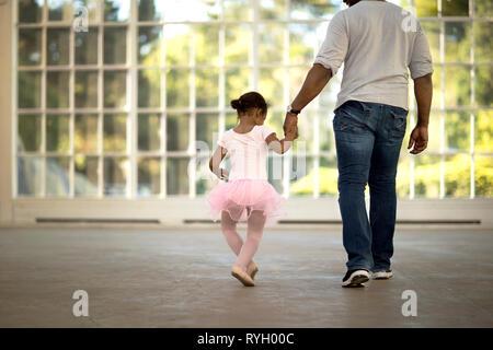 Mitte der erwachsenen Mann hält die Hand seiner jungen Tochter. - Stockfoto