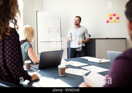 Manager erklärt ein kreatives Konzept während einer Whiteboard-präsentation zu einer Gruppe von Angestellten an einem Tisch in einem Büro Sitzungssaal - Stockfoto