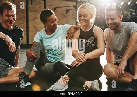 Lächelnd Gruppe von diversen Freunden in Sportkleidung reden, während er auf dem Gym, nach dem Training - Stockfoto