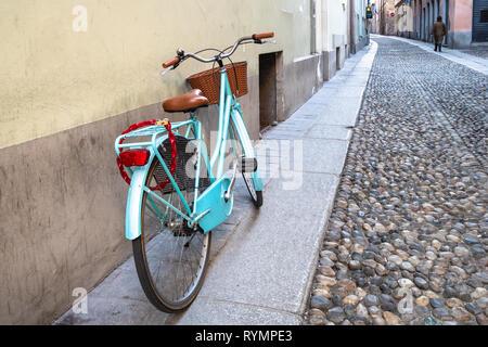 Reisen nach Italien - Fahrradverleih in der Nähe der Wand des Hauses auf mittelalterlichen Straße mit Kopfsteinpflaster in Pavia Stadt, Lombardei in Abend - Stockfoto
