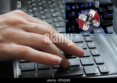 Die Hand des Mädchens auf der Tastatur schließen oben mit dem Konzept der digitalen Technologie auf dem Kauf und Verkauf von crypto Währung bitcoin mit einer Flagge von Do - Stockfoto