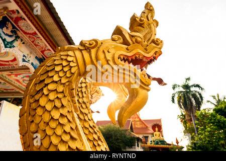 Einen atemberaubenden Blick auf einen wunderschönen Gold - überdachte Naga (Schlange Menschen) vor der Wat That Luang Tai während des Sonnenuntergangs. Vientiane, Laos. Nagas sind mythische se - Stockfoto