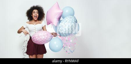 Alles Gute zum Geburtstag! Positive junge afro-amerikanische Frau mit lockigem Haar hält ein Bündel von bunten Luftballons und Lachen. Web Banner. 16:9-Format. Glück Konzept - Stockfoto