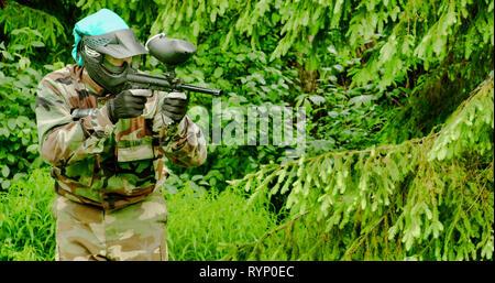Ein Mann mit Camouflage Outfit ist ein Paintball spielen 4K FS 700 Odyssey 7 Q - Stockfoto