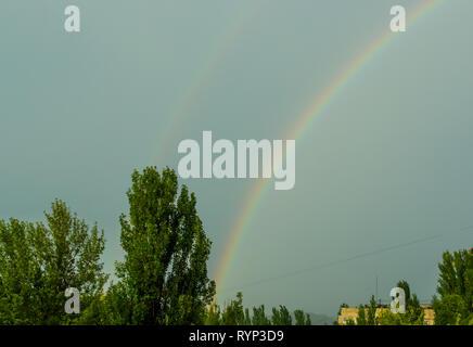 Natürliche doppelten Regenbogen über grüne Bäume, Sommer Stadt Landschaft - Stockfoto